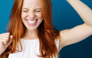 Woman with ginger hair smiling with hands in the air