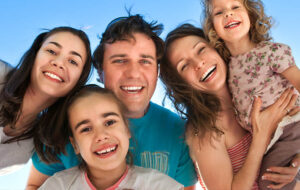Young family of five smiling into camera