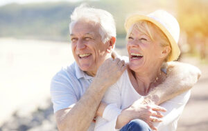 Older couple on the beach laughing