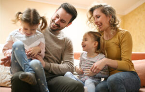 Young family with two girls playing and laughing at home