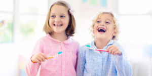 Two young girls smiling and laughing before brushing their teeth