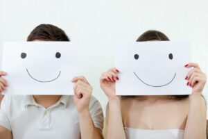 Man and woman holding up paper smiley faces in front of their own faces.