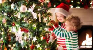 Two young kids helping to decorate a Christmas tree