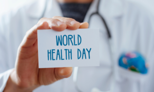 Medical professional holding a smal sign that says world health day