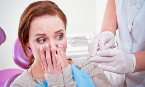Women hold hands to her face at dentist practice