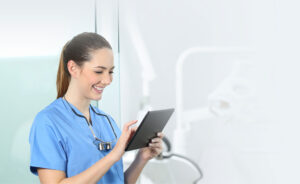 Smiling female dentist look at a tablet device